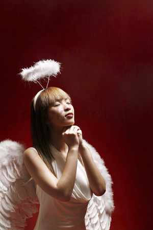 Religion : Young woman in angel costume making a wish