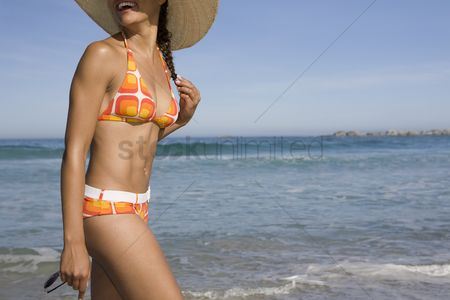 Retro : Young woman in sunhat and retro swimwear walking on beach