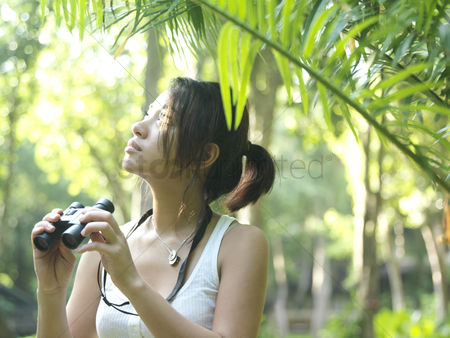Ponytail : Young woman in tropical forest holding binoculars