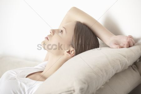 Ponytail : Young woman lies relaxing with hand behind head