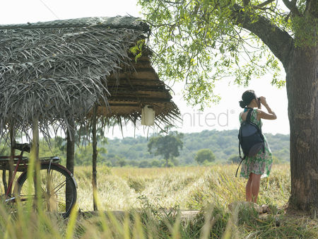 Ponytail : Young woman looking through binoculars bicycle under thatched roof