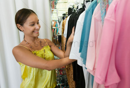 Choosing : Young woman looking through clothing rack in store