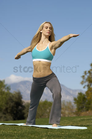 Grass : Young woman performing yoga exercises in park