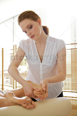 Club : Young woman receiving foot massage from masseuse