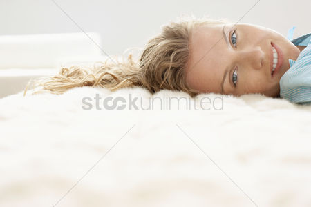 Smiling : Young woman relaxing on bed portrait