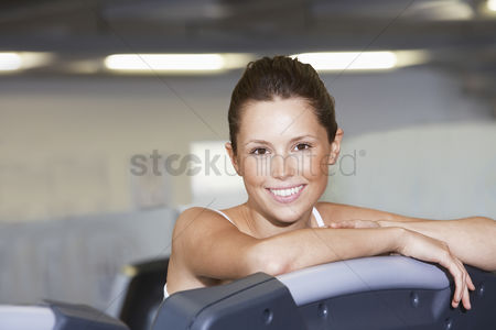 Club : Young woman resting on treadmill at health club portrait