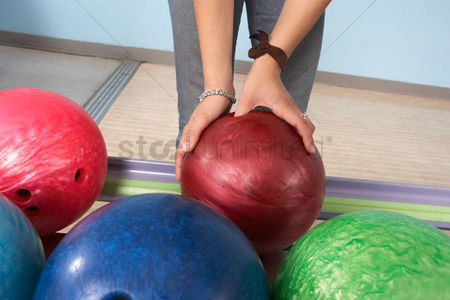 Variety : Young woman selecting bowling ball mid section