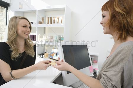 Profession : Young woman serving a customer in the hairdressers