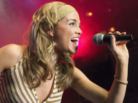 Arts : Young woman singing on stage in concert side view