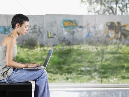 Denim : Young woman sitting down using laptop indoors