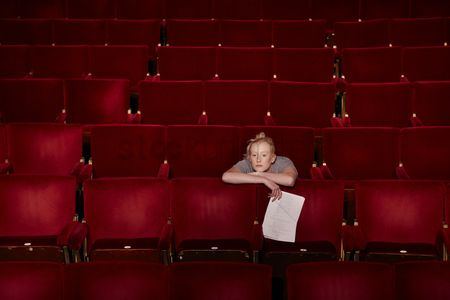 Arts : Young woman sitting in theatre stalls