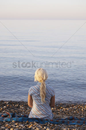 Ponytail : Young woman sitting on beach back view