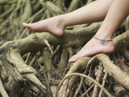 Asian : Young woman sitting on tree roots close-up on foot