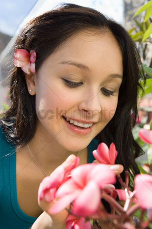 Greenhouse : Young woman smelling exotic plat in greenhouse  close-up