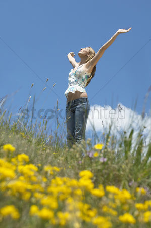Denim : Young woman standing in field with open arms low angle view side view