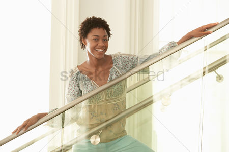Stairs : Young woman standing on modern stairs portrait