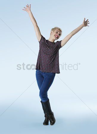 Spirit : Young woman standing with arms outstretched and laughing