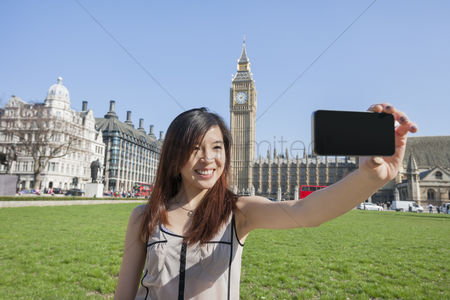 England : Young woman taking self portrait through smart phone against big ben at london  england  uk