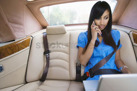Car : Young woman talking on phone and using laptop in car