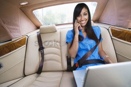 Posed : Young woman talking on phone in car
