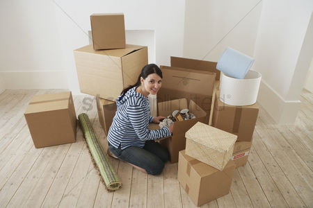 Pile : Young woman unpacking boxes