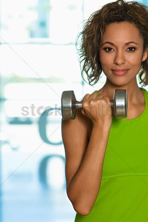 Dumbbell : Young woman using dumbbell indoors  portrait