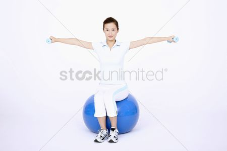 Dumbbell : Young woman using dumbbells while sitting on fitness ball
