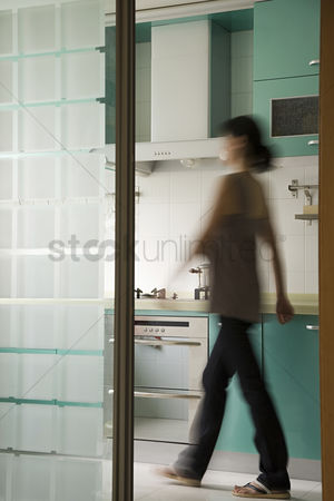 Housewife : Young woman walking in a kitchen