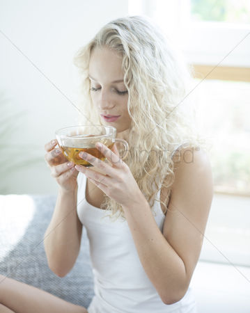 Czech republic : Young woman with eyes closed enjoying herbal tea in house