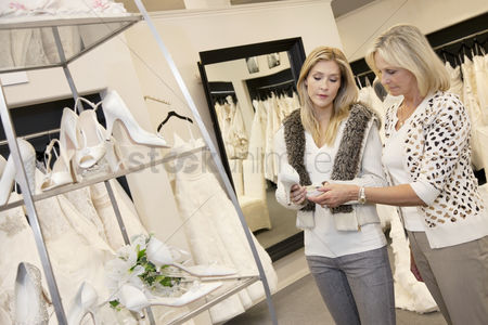 Offspring : Young woman with senior mother looking at footwear in bridal store