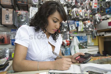 Hispanic : Young woman working in mobile phone shop