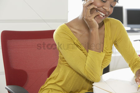 Finger : Young woman writing at desk in office