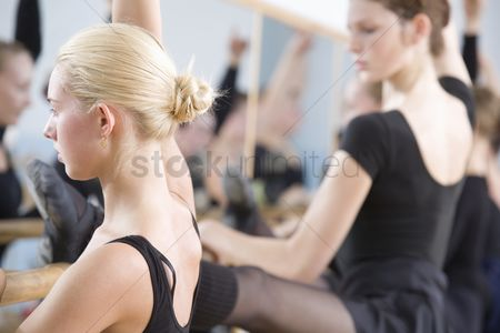 Arm raised : Young women practise ballet at the barre