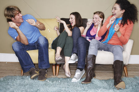 Friends : Young women throwing popcorn at friend on sofa